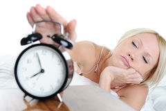 Sleepy woman turns off the alarm Stock Photo
