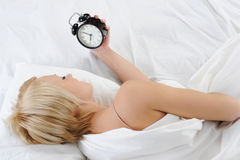 Sleepy woman turns off the alarm Royalty Free Stock Photos
