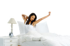 Sleepy yawn. Yawn stretch sleepy latino woman in bed waking up to the sound of her alarm clock  on white background Stock Photos
