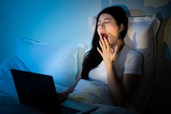 Sleepy yawn tired woman sitting on cosy bed. With laptop in bedroom. mixed race asian chinese model Stock Image