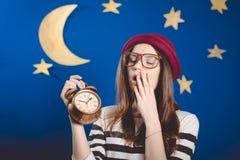Sleepy yawning beautiful girl holding clocks on Royalty Free Stock Images