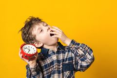 Sleepy and yawning schoolboy with alarm clock on yellow background. Funny boy yawns wide, covering his mouth with hand. Emotion stock image