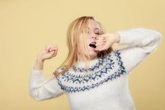Sleepy yawning teenage woman in jumper Stock Photos