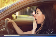 Sleepy yawning woman driving her car after long hour trip. stock photography