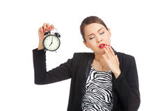 Sleepy young Asian business woman with a clock in the morning Royalty Free Stock Image