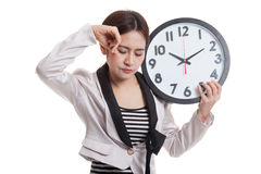 Sleepy young Asian business woman with a clock in the morning. Royalty Free Stock Image