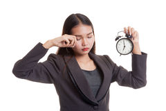 Sleepy young Asian business woman with a clock in the morning. Royalty Free Stock Images