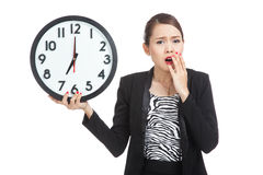 Sleepy young Asian business woman with a clock in the morning Stock Images