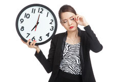 Sleepy young Asian business woman with a clock in the morning Stock Photography