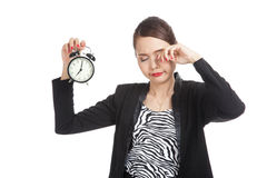 Sleepy young Asian business woman with a clock in the morning Stock Photos