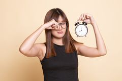 Sleepy young Asian woman with a clock in the morning. On beige background stock image