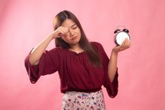 Sleepy young Asian woman with a clock in the morning. On pink background stock photography