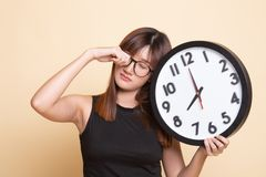 Sleepy young Asian woman with a clock in the morning. On beige background royalty free stock image