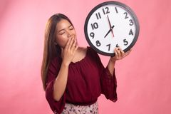 Sleepy young Asian woman with a clock in the morning. On pink background royalty free stock images