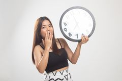 Sleepy young Asian woman with a clock in the morning. On white background stock images