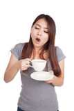 Sleepy young Asian woman yawn with cup of coffee Royalty Free Stock Photography