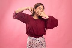 Sleepy young Asian woman yawn. On pink background royalty free stock photo