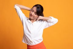Sleepy young Asian woman yawn. On yellow background royalty free stock photography