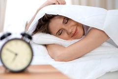 Sleepy young brunette woman stretching hand to ringing alarm willing turn it off. Early wake up, not getting enough. Sleep concept Stock Photography
