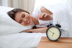 Sleepy young brunette woman stretching hand to ringing alarm willing turn it off. Early wake up, not getting enough. Sleep concept Stock Photo