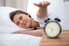 Sleepy young brunette woman stretching hand to ringing alarm willing turn it off. Early wake up, not getting enough. Sleep concept Royalty Free Stock Photo