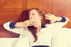 Sleepy Young Business Woman Yawning Lies In Bed Trying To Wake Up Stock Photo