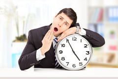 Sleepy young businessman leaning his head on a big wall clock, i Royalty Free Stock Photography