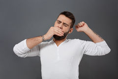 Sleepy young handsome man yawning over grey background. Royalty Free Stock Images