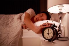 Sleepy young man in bed with extending hand to alarm clock Stock Images