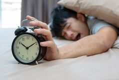 Sleepy young man in bed with eyes closed extending hand to alarm. Clock Royalty Free Stock Photography