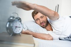 Sleepy young man in bed reaching to turn off the. Alarm clock stock photography