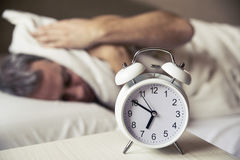 Sleepy young man covering ears with pillow as he looks at alarm clock in bed. Sleeping man disturbed by alarm clock early morning. Frustrated man listening to Royalty Free Stock Photo