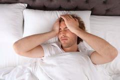 Sleepy young man lying on pillow stock photos