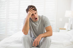 Sleepy young man sitting and yawning in bed Stock Photo