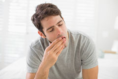 Sleepy young man sitting and yawning in bed Stock Images