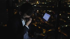Tired sleepy man is working on his computer at night near the window with cityscape. Sleepy young man in suit is working on his computer at night near the stock footage