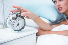 Sleepy young woman in bed extending hand to alarm clock Stock Photos