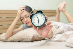 Sleepy young woman in bed with eyes closed extending hand to ala stock photography