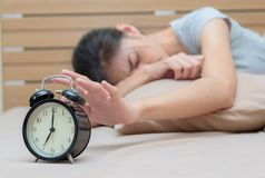 Sleepy young woman in bed with eyes closed extending. Hand to alarm clock stock photography