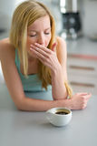 Sleepy young woman with cup of coffee in kitchen Royalty Free Stock Images