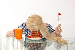 Sleepy young woman had breakfast and put her head in a plate, fell asleep in a plate. The concept of early morning, heavy morning. royalty free stock image