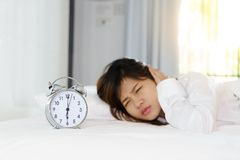 Sleepy young woman looking at alarm clock with hands covering he. R ears in the morning. early wake up Royalty Free Stock Photo