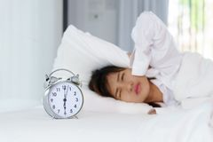 Sleepy young woman looking at alarm clock with hands covering he. R ears in the morning. early wake up Royalty Free Stock Image
