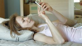 Morning. Awakening women in bed. Sleepy Young woman with red hair in pink clothes on the bed, uses the phone and smiles. Morning stock video