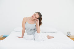 Sleepy young woman sitting in bed Stock Photo