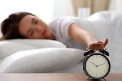 Sleepy young woman stretching hand to ringing alarm willing turn it off. Early wake up, not getting enough sleep. Getting work concept Stock Image