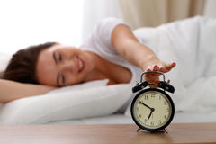 Sleepy young woman stretching hand to ringing alarm willing turn it off. Early wake up, not getting enough sleep. Getting work concept Stock Photography