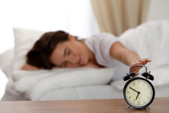 Sleepy young woman stretching hand to ringing alarm willing turn it off. Early wake up, not getting enough sleep. Getting work concept Stock Photo