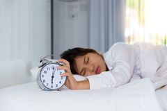 Sleepy young woman stretching hand to trying kill alarm clock in Royalty Free Stock Images
