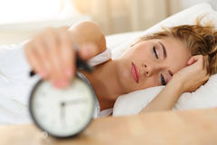 Sleepy young woman trying kill alarm clock Royalty Free Stock Photography